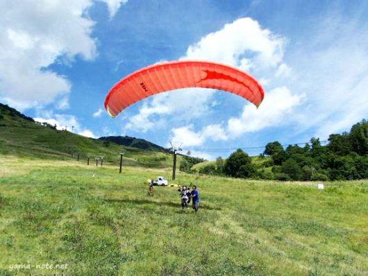 パラグライダーで飛ぶ男性