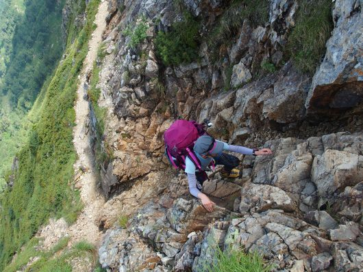 北アルプスの岩場を登る女性